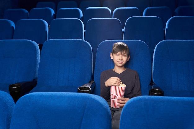 Piccolo spettatore maschio seduto da solo nel cinema e sorridente