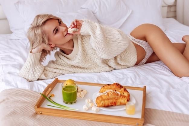 小さなマシュマロ。ベッドで冷やしながら小さなマシュマロを食べるスリムでセクシーな格好良い女性