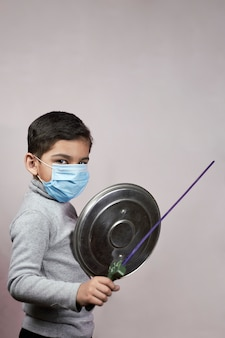 Little moddle-eastern kid in face mask having fun during covid-19 quarantine