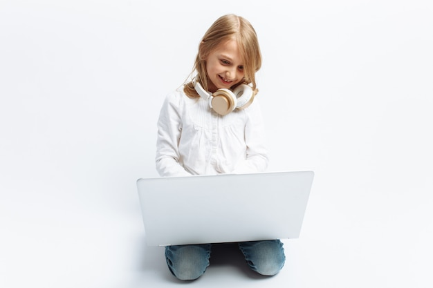 Little modern girl sitting with laptop and listening to music, cute and beautiful