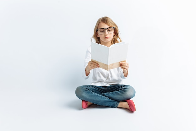 Little modern girl with glasses reading a book and dreaming, cute and beautiful