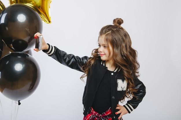 Маленькая современная хипстерская девочка в модной одежде и воздушных шарах, селфи. сфотографируй на телефон