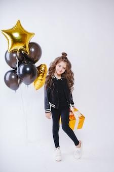 ファッションの服のモダンな内気な少女は風船の近くに立って、金の存在を保持します。お誕生日。