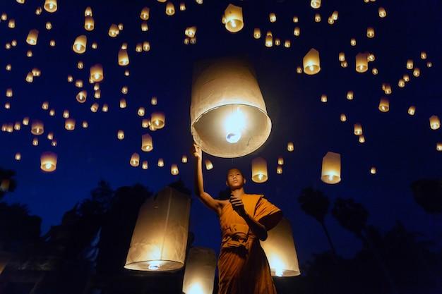작은 승려가 떠 다니는 등불의 불을 피우고, 태국 불교 승려가 등불을 떠