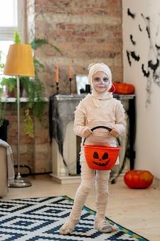 Little mummy holding pumpkin bucket for treats