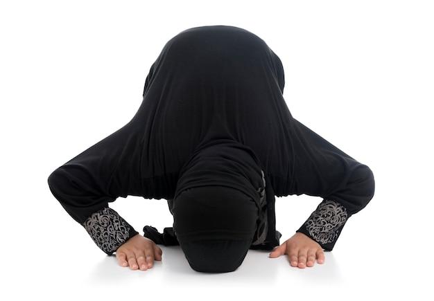 Маленькая мусульманская девочка молится в традиционном костюме