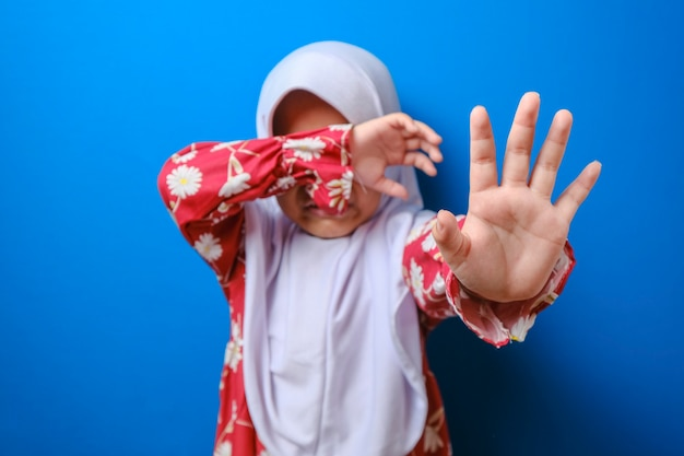 Little muslim girl suffering bullying raises her palm asking to stop the violence