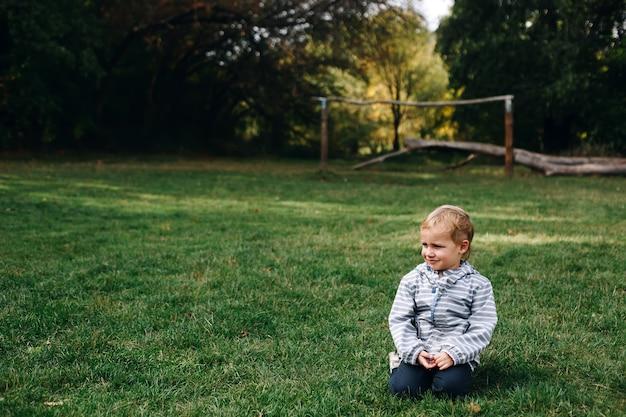 小さないたずらな男の子は笑顔で緑の牧草地に座って、屋外でアクティブな幸せな子供時代