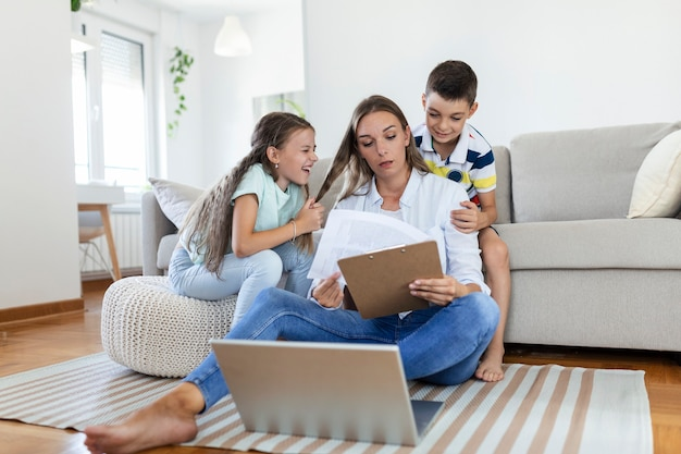 집에서 노트북으로 일하는 바쁜 젊은 여성을 산만하게 하는 작은 장난꾸러기 아이들