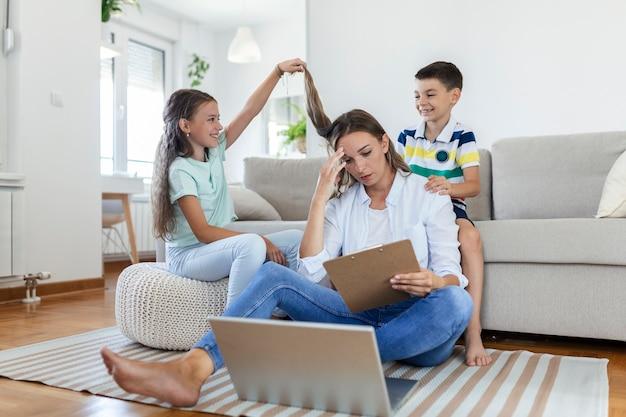 忙しい若い女性を自宅のラップトップでの仕事からそらす小さないたずらな子供たち