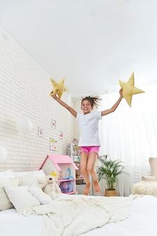 Маленькая непослушная девочка прыгает на кровати в детской комнате