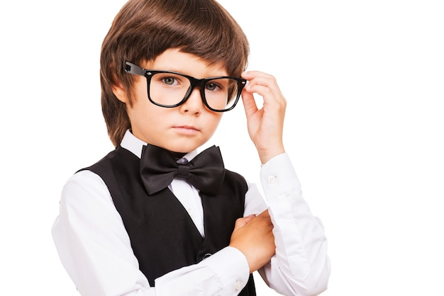 Little nerd. cute little boy adjusting his glasses and looking at camera while standing isolated on white