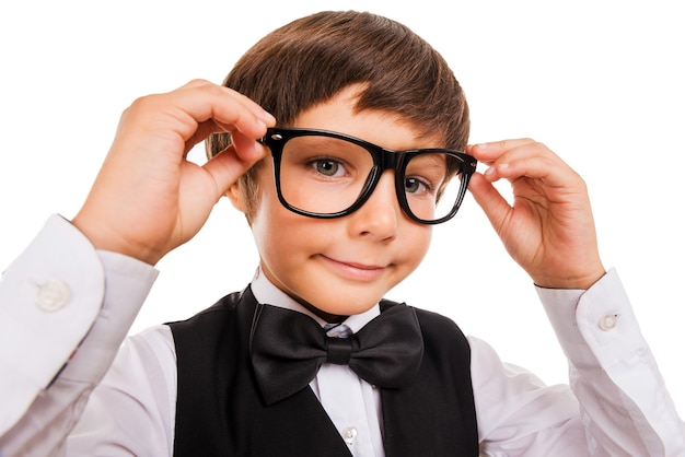 Little nerd. wide angle image of cute little boy adjusting his glasses and looking at camera while isolated on white