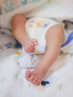 小さな新生児の足がクローズアップ