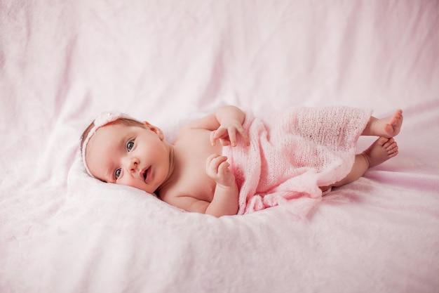 ピンクの背景にピンクのスーツを着た小さな新生児。母性。