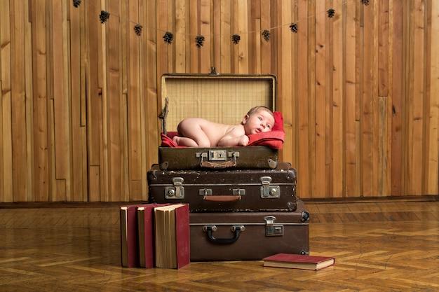 スーツケースに横になっている小さな生まれたばかりの赤ちゃん