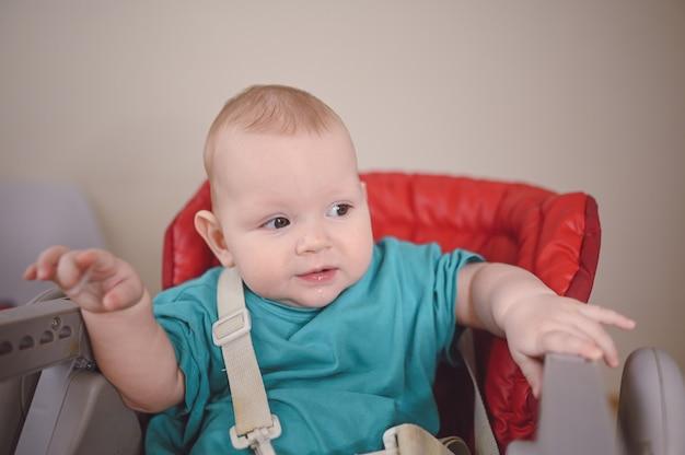 Маленький новорожденный ребенок сидит на стульчике для кормления