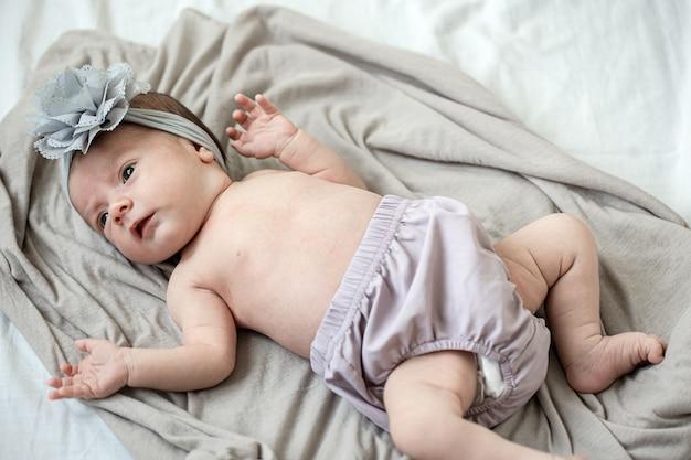 頭に包帯を巻いた小さな新生児は、柔らかい毛布の上に横たわっています。