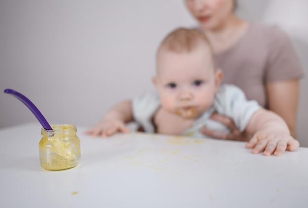 숟가락으로 유리 항아리에서 야채 또는 과일 퓌레를 먹는 것을 배우는 작은 갓난 재미있는 아기