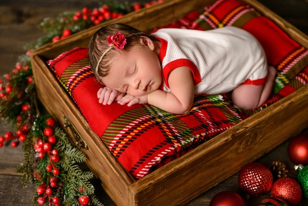 Little newborn girl eight days old in christmas suit