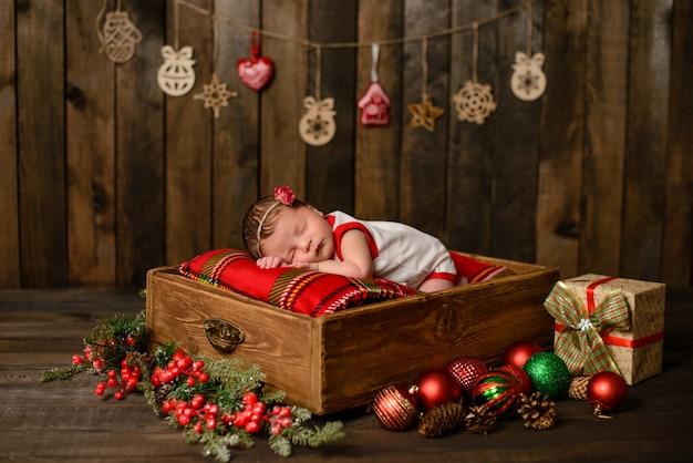 Маленькая новорожденная девочка восемь дней в рождественском костюме