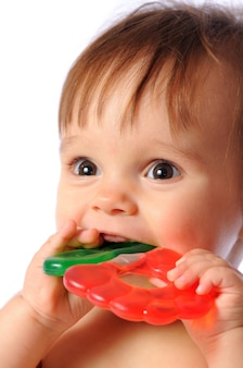 小さな1歳の赤ちゃんは、カラフルな歯が生えるおもちゃを手に持っています。子供の歯がおもちゃを噴出します。孤立した白い背景の上の肖像画