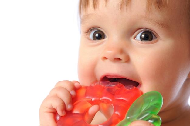 小さな1歳の赤ちゃんが手にカラフルな歯が生えるおもちゃを持っています