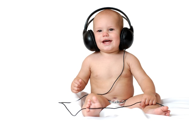 Little one year old boy listens to music in big headphones and smiles on an isolated white background