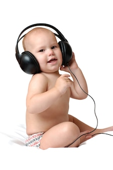 Little one year old boy listens to music in big headphones
