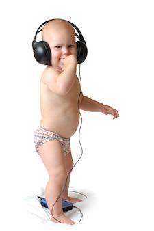 小さな1歳の少年は、大きなヘッドフォンで音楽を聴き、孤立した白い背景で笑顔