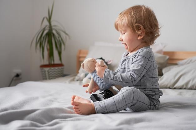 彼のお気に入りのおもちゃでベッドで遊んでいる小さな1歳の男の子ライフスタイルの写真