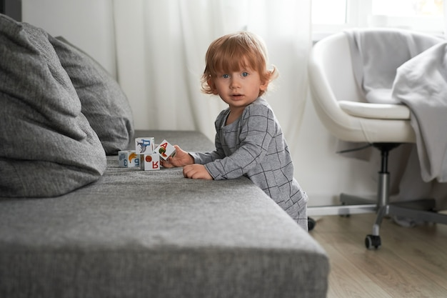 文字と彼のおもちゃの立方体でソファで遊んでいる小さな1歳の男の子ライフスタイルの写真