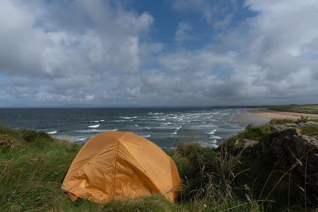 崖の端にある小さなオレンジ色のテント