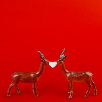 Little ornament heart between toy deer
