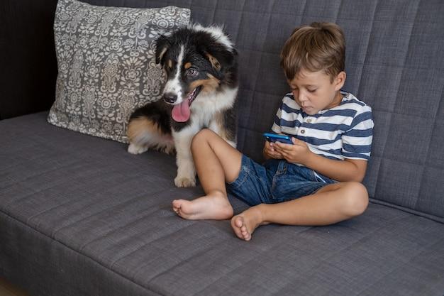 작은 주인 행복한 소년은 전화를 걸고 소파에 호주 양치기 강아지와 함께 앉아 있습니다. 세 가지 색상. 가장 친한 친구. 장치 중독.