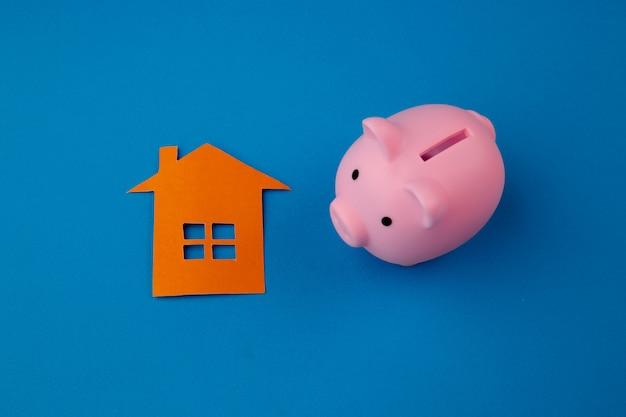 青色の背景に貯金箱の横にある小さな紙の家