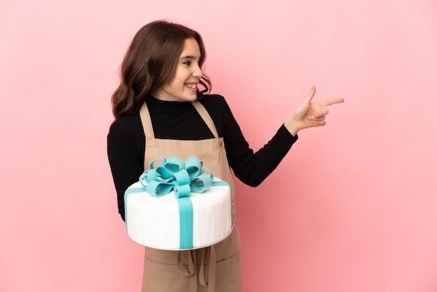ピンクの背景に分離された大きなケーキを持って横に指を指し、製品を提示する小さなパティシエ