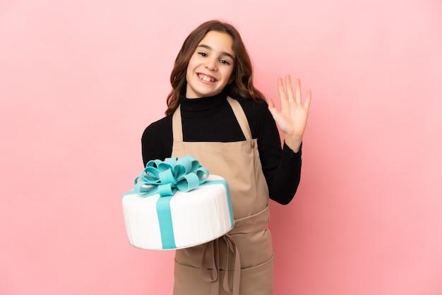 행복 한 표정으로 손으로 경례 분홍색 배경에 고립 된 큰 케이크를 들고 작은 생 과자 요리사