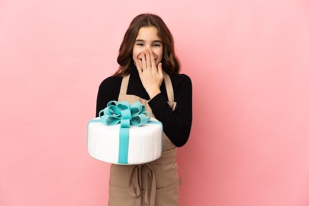 ピンクの壁に分離された大きなケーキを持っている小さなパティシエは幸せで笑顔で口を手で覆っています