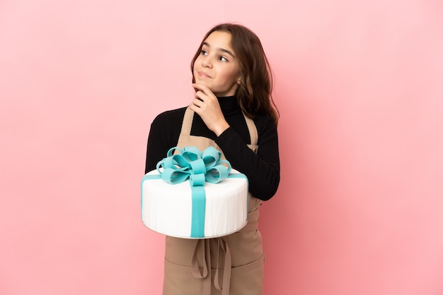 Little pastry chef holding a big cake isolated on pink background and looking up