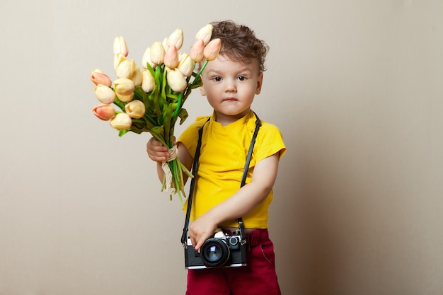Little photographer, a child with a camera in their hands and flowers. bouquet of tulips for mother's day.