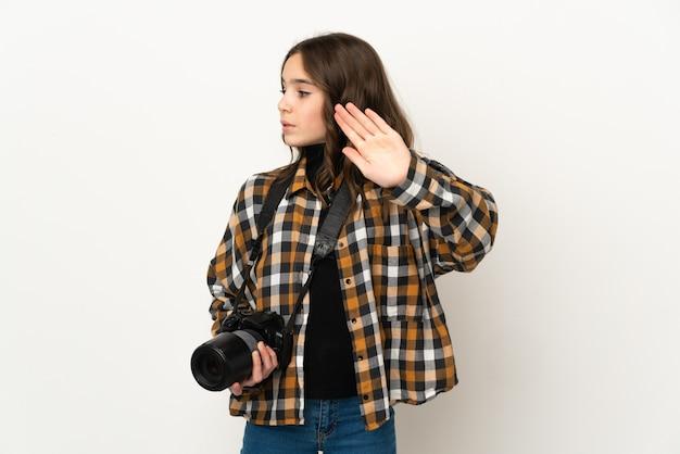 Маленькая девочка-фотограф изолирована на фоне, делая жест стоп и разочарована