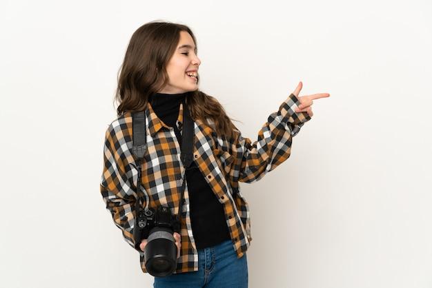 Маленькая девочка-фотограф изолирована на фоне, указывая пальцем в сторону и представляет продукт