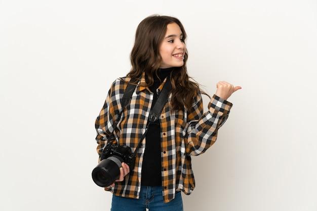 제품을 제시하기 위해 측면을 가리키는 배경에 고립 된 작은 사진 작가 소녀