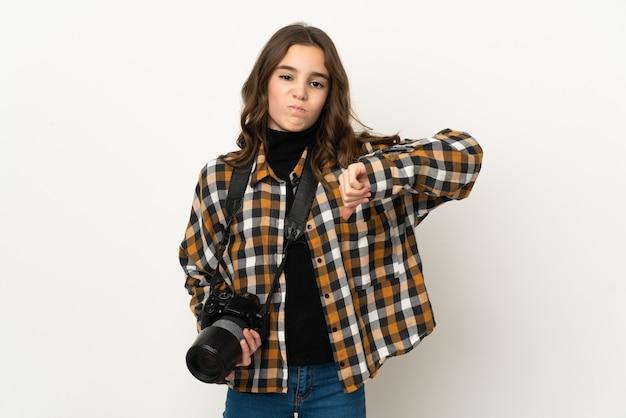 否定的な表現で親指を下に示す背景に分離された写真家の少女