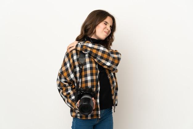 努力したために肩の痛みに苦しんでいる背景に孤立した小さな写真家の女の子