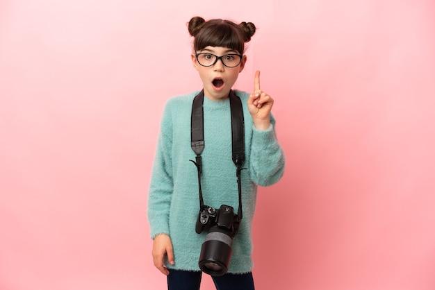 Маленькая девочка-фотограф изолирована на розовом фоне, намереваясь реализовать решение, подняв палец вверх