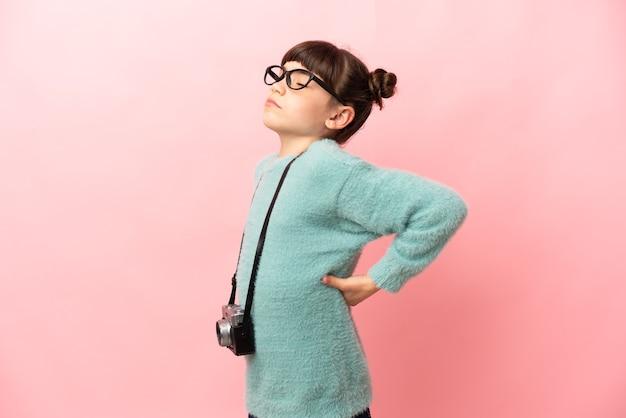Маленькая девочка-фотограф изолирована на розовой стене и страдает от боли в спине из-за того, что приложила усилия