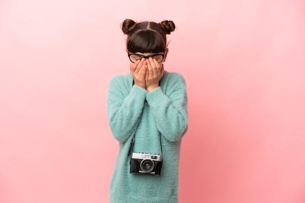 疲れて病気の表情でピンクに分離された小さな写真家の女の子