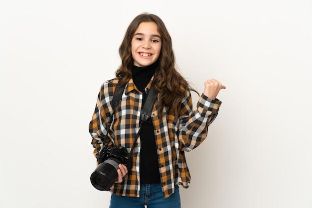 제품을 제시하기 위해 측면을 가리키는 벽에 고립 된 작은 사진 작가 소녀